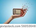 Female hand holding old radio set shattering into pieces on blue background 56050648
