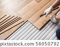Installing laminated floor, detail on man hands holding hammer in textile gloves, over white foam 56050792
