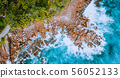 Aerial drone view of tropical coastline with turquoise ocean waves splashing against bizarre granite 56052133