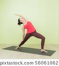 Asian woman doing warrior pose yoga. 56061062