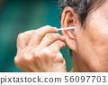Senior woman's hand hold a cotton swab clean ear 56097703