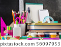 Stationery on a table in front of blackboard. 56097953