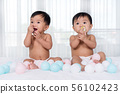 cheerful twin babies on bed 56102423