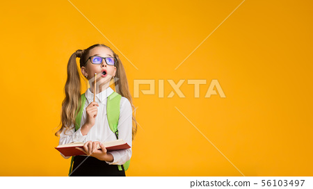 Curious First-Grade Schoolgirl Holding Opened Book And Pencil 56103497