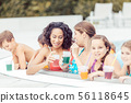 Family with glasses of juice in swimming pool 56118645