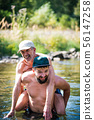 Father and son having fun in the river water 56147258