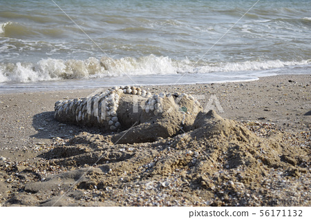 Sand sculpture of a mermaid decorated with shells 56171132