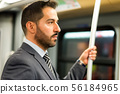 Businessman hanging to a pole in a train in the 56184965