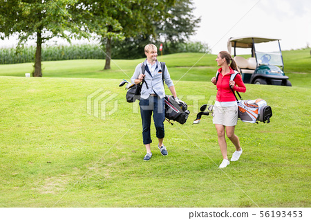 Golfing couple carrying their bags 56193453