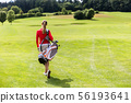 Rear view of woman carrying golf bag 56193641