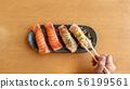 chopsticks tong fresh salmon sushi on a wooden 56199561