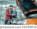 Consultant of car showroom explaining construction of the automobile. 56200616