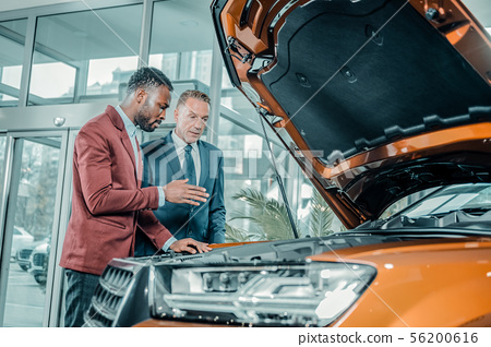 Consultant of car showroom explaining construction of the automobile.