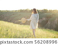 Happy woman with a straw hat in her hands walking on top of the edge of a mountain cliff under the 56208996