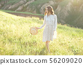 Happy woman with a straw hat in her hands walking on top of the edge of a mountain cliff under the 56209020