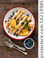 Sweet crepes filled with fresh blueberry and peach 56216985