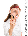 Young doctor looking through a magnifying glass 56231007