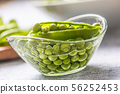 Fresh green pea seeds in bowl on kitchen table 56252453