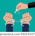 Hand with key unlocking handcuffs. 56254247