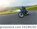 Motorcycle driver riding in Alpine landscape. 56286282
