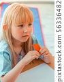 Pretty blonde girl having modeling clay in her hand 56336482
