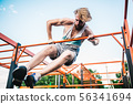 strong athlete doing pull-up on horizontal bar. Muscular man doing pull ups on horizontal bar in 56341694