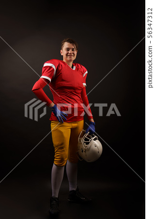 Picture of happy american brunette woman soccer player with helmet in her hand 56347312