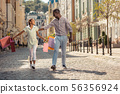 Happy teenager walking with colorful shopping bags 56356924