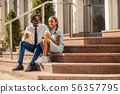 Pleased dad and kid sitting on stairs near house 56357795