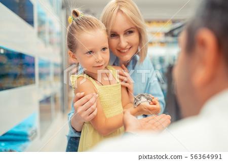 Girl wearing dress holding hamster standing near mommy 56364991
