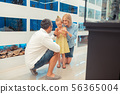 Parents standing near daughter holding and looking at hamster 56365004