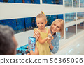 Daddy taking photo of daughter holding little hamster in hands 56365096