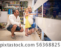 Girl pointing finger while standing in aquarium with parents 56368825