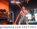 Serious young man holding ropes in his hands 56371041