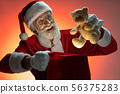 Mature aged Santa Claus packing toy inside sack 56375283