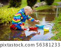 Child with paper boat in puddle. Kids by rain. 56381233
