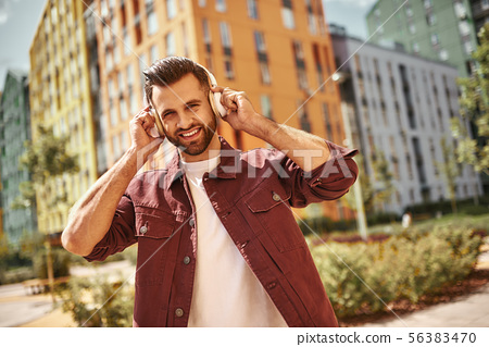 Good mood. Handsome and happy young man with stubble in headphones listening to the music and 56383470