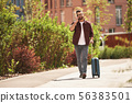 Happy to hear you Cheerful bearded man in casual wear and eyeglasses pulling his luggage and talking 56383501