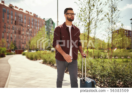 Time for adventure. Handsome and young bearded man in casual wear and eyeglasses pulling his luggage 56383509
