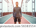 Confident sportsman. Portrait of young and handsome bearded man in sports clothing standing on the 56383554