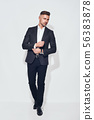 Perfect style. Full length of handsome bearded businessman in classic suit adjusting sleeves and 56383878