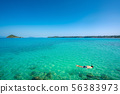 Tourists snorkel in crystal turquoise water near 56383973