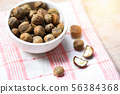 Chestnuts uncooked in bowl on the table / genus 56384368