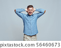 Bla bla bla. Depressed man closing ears with both hands and screaming while standing against grey 56460673