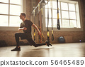 TRX Training. Young athletic man in sports clothing training legs with trx fitness straps in the gym 56465489