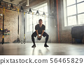 Weight exercise. Handsome and strong young man in sports clothing exercising with dumbbells while 56465829