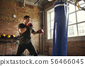 Strong and motivated. Young and sporty man boxing in gloves in a loft style gym. Boxer 56466045