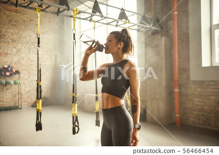 Refreshing. Side view of young athletic woman in earphones with tattoos on her hands is drinking 56466454