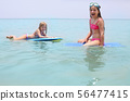 Little girls with surfing boards playing on 56477415