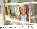 Portrait of girl smiling through panoramic window 56547518